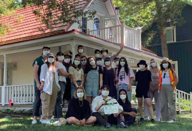 'Little Bird' cast and crew wearing protective masks standing before a house on set